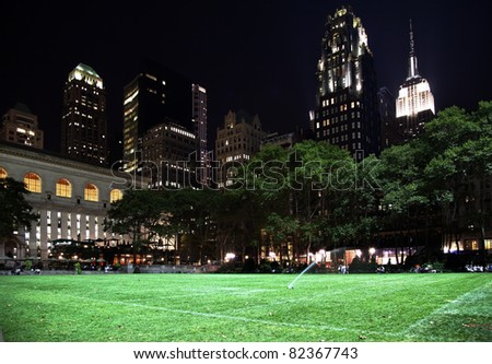 Bryant Park New York City Green Grass Skyline Apartment Buildings Empire State Building Night - stock photo