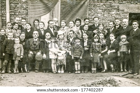 BRZESKO NOWE, POLAND, CIRCA FORTIES - Vintage photo of big multigenerational family with children posing during a wedding party - stock photo
