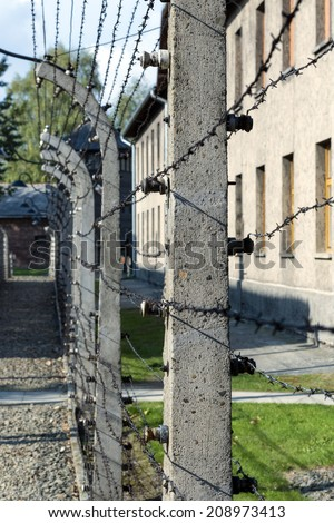 BRZEZINKA, POLAND - OCTOBER 13, 2012: Electrified barbed-wire fences in Auschwitz II-Birkenau camp in Brzezinka, Poland. Concentration Camp refers to a network of different camps built by the Nazis. - stock photo