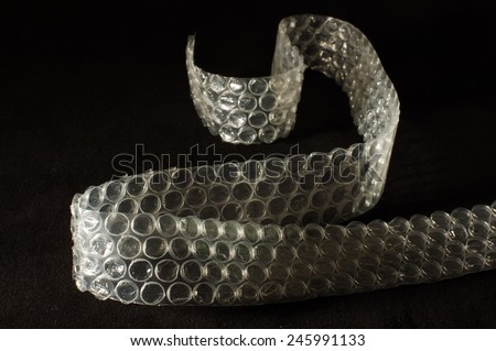 Bubble wrap packing and shipping equipment isolated on the black background - stock photo
