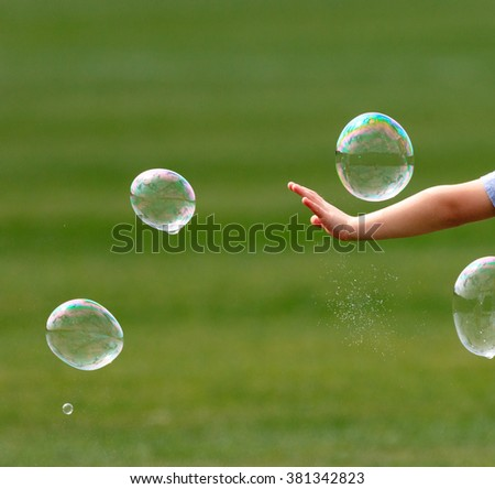 bubbles being burst by child hand - stock photo