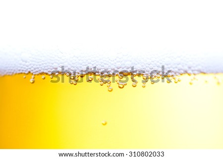Bubbles of beer froth in glass - stock photo