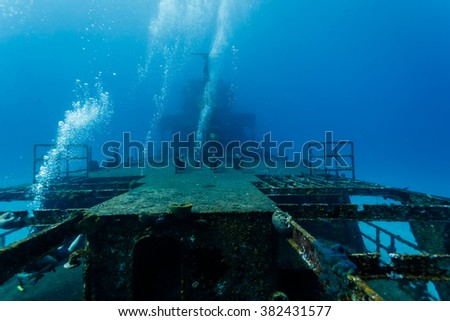 Bubbles rising from divers exploring large shipwreck in Caribbean - stock photo
