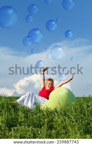 Bubbling vitality - woman on spring grassland enjoying sunshine - stock photo