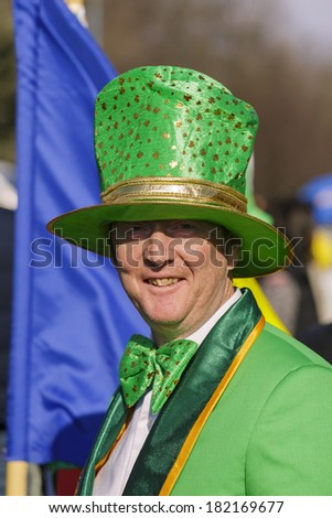 BUCHAREST - MARCH 16: Unidentified man wearing traditional Irish green hat and costume shares a smile during the 2nd St. Patrick's Day Parade on March 16, 2014 in Bucharest, Romania. - stock photo