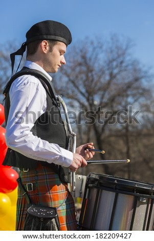 BUCHAREST - MARCH 16: Unidentified young man wearing traditional Irish clothes plays the drum during the 2nd St. Patrick's Day Parade on March 16, 2014 in Bucharest, Romania. - stock photo