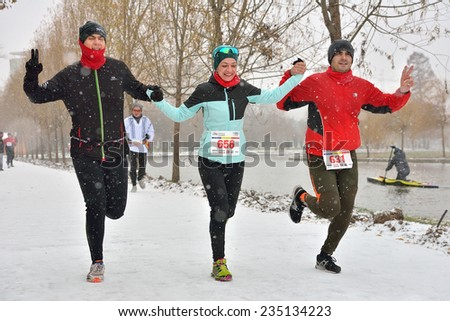 BUCHAREST, ROMANIA - DECEMBER 1st: Happy unidentified marathon runners compete while snowing, at the National Day of Romania Marathon 2014, December 1st, 2014 in Bucharest, Romania  - stock photo