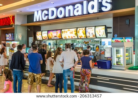 BUCHAREST, ROMANIA - JULY 20, 2014: People buying fast-food from McDonald's Restaurant. McDonald's is the main fast-food restaurant chain in Romania. - stock photo