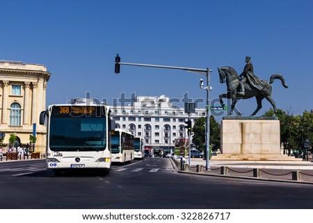 BUCHAREST, ROMANIA - JULY 15: Public transportation on July 15, 2012 in Revolution Square in Bucharest, Romania. Modern bus in traffic in Bucharest downtown - stock photo