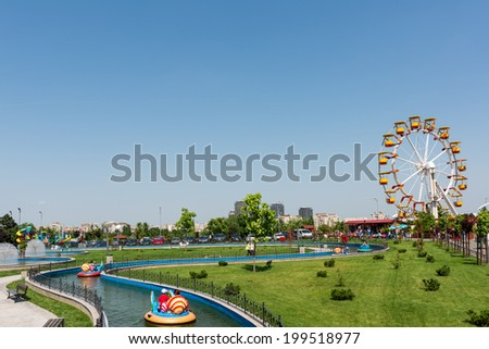 BUCHAREST, ROMANIA - JUNE 08, 2014: Children On Boat Ride In Youths Public Amusement Park (Tineretului Park) On Summer Day. Created in 1965 is one of the largest fun parks in south Bucharest. - stock photo