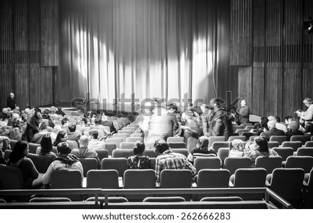 BUCHAREST, ROMANIA - MARCH 22, 2015: Black And White Photo Of People Taking Their Seats In Theater Inside. - stock photo