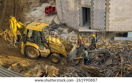 BUCHAREST, ROMANIA - MARCH 19, 2015: Workers filling a bulldozer bucket with wood scraps in a large construction site near Promenada mall - stock photo