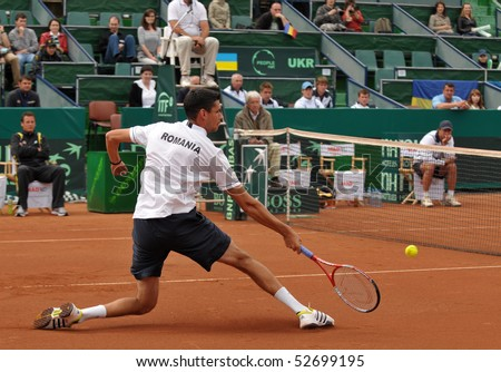 BUCHAREST, ROMANIA - MAY 9: Romanian Victor Hanescu is stretching after a ball during the fourth match of the Davis Cup meeting between Romania and Ukraine at the BNR Arenas on May 9, 2010 in Bucharest, Romania. - stock photo
