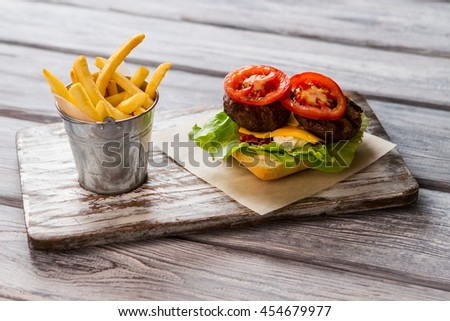 Bucket filled with fries. Tomato slice and grilled meat. Ingredients for tasty hamburger. You should taste this. - stock photo