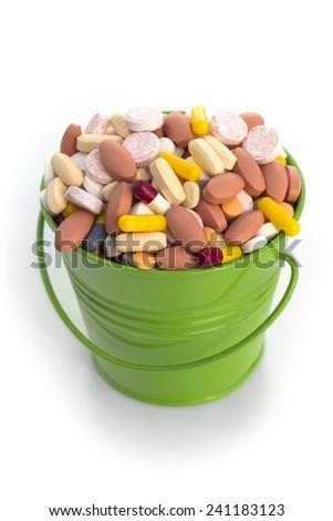 Bucket full of drugs.  --  Bucket full of pills and capsules on white background. - stock photo