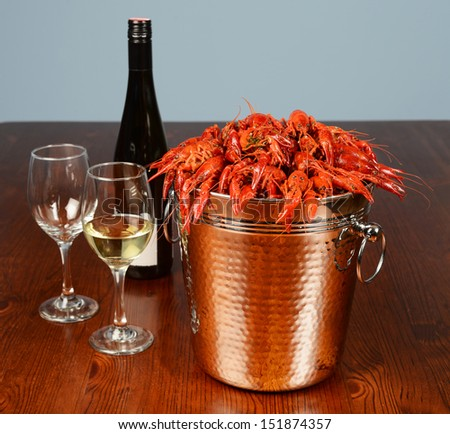 bucket full of river lobsters served with wine and glasses - stock photo