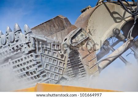 Bucket of Hydraulic Mining Excavator unloading ore into heavy dump truck at the opencast mining - stock photo