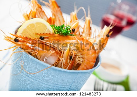 Bucket of king prawns on ice with lemon, sauce and two glasses of wine - stock photo