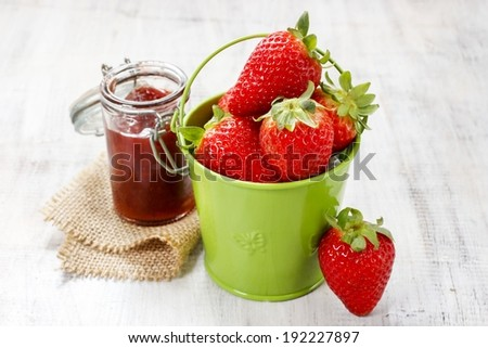 Bucket of strawberries on wooden table - stock photo