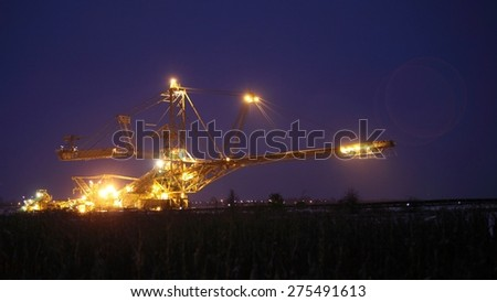 bucket wheel excavator digging for brown coal night view Poland extractive industry - stock photo
