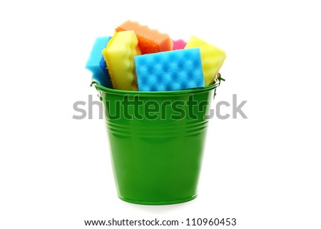 Bucket with colored sponges for cleaning on a white background. - stock photo