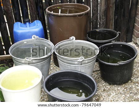 Buckets in zinc and plastic filled with collected rainwater for watering garden - stock photo