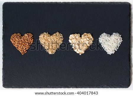 Buckwheat, brown rice, oatmeal and milk rice in a shapes of hearts - stock photo