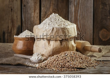 buckwheat flour and buckwheat, rolling pin, spoon on the old wooden background closeup - stock photo
