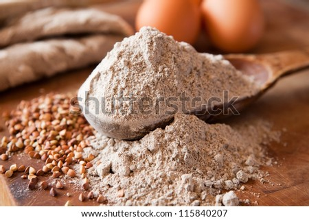 Buckwheat flour in a wooden measuring spoon - stock photo
