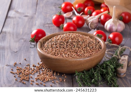 Buckwheat in a bowl with tomato, garlic and thyme on wooden boards - stock photo