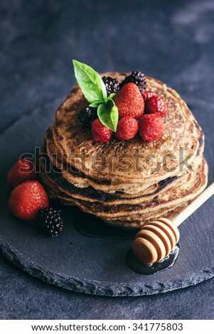 Buckwheat pancakes with berry fruit and honey on dark background,selective focus  - stock photo