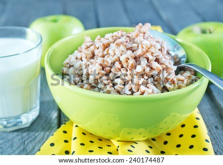 Buckwheat porridge in a bowl and green apples on a wooden table - stock photo