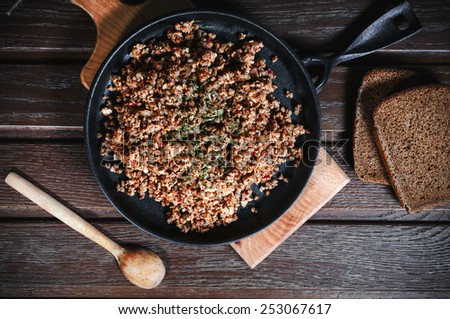 buckwheat with minced meat and vegetables on the wooden table - stock photo
