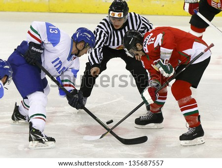 BUDAPEST - APRIL 19: Hungarian Sikorcin (R) and Italian di Casmirro during Hungary vs. Italy IIHF World Championship ice hockey match at Budapest Sportarena on April 19, 2013 in Budapest, Hungary. - stock photo