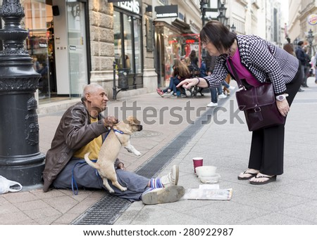 Budapest, Hungary - April 30, 2015: An old man is begging in front of a fashion shop in a main street in Budapest, Hungary. - stock photo