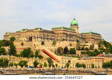 BUDAPEST, HUNGARY - APRIL 29 2014: Buda Castle in Budapest. Historic Royal Palace at Castle Hill .View  from across the Danube River in the morning. Other buildings and reflections can be seen - stock photo