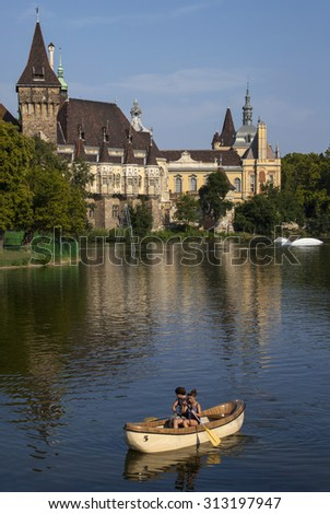 BUDAPEST, HUNGARY - AUGUST 14TH 2015: Tourists rowing a boat on the lake in City Park with Vajdahunyad Castle in the background in Budapest, on 14th August 2015. - stock photo