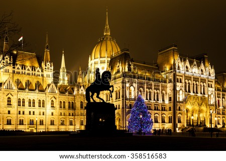 BUDAPEST, HUNGARY - DEC 19 2015: Tourists enjoy the Christmas lights at the Parliament House in Budapest, Hungary. This traditional Christmas fair attracts abut 700,000 visitors each year. - stock photo