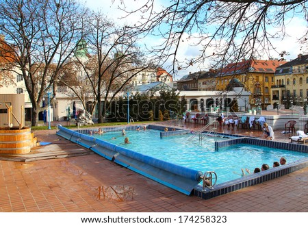 BUDAPEST, HUNGARY - JANUARY 4, 2013: People enjoy an outdoor thermal pool in the Gellert Medicinal Bath - one of the most famous baths in Budapest opened in 1918 - stock photo