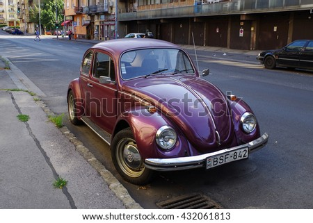Budapest, Hungary - July 9, 2015: Purple retro economy car - Volkswagen Beetle parked on the street of Budapest.  - stock photo