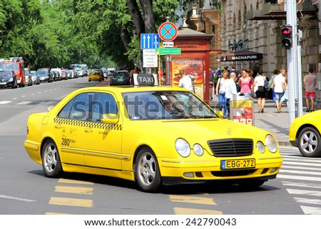 BUDAPEST, HUNGARY - JULY 23, 2014: Yellow taxi car Mercedes-Benz W210 E-class at the city street. - stock photo