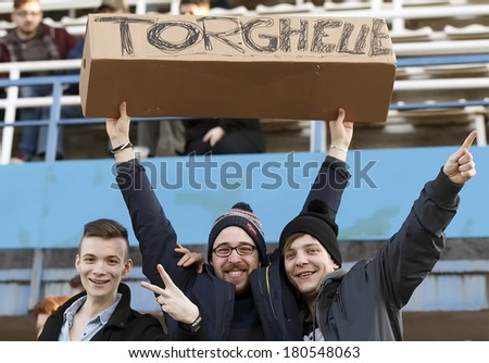 BUDAPEST, HUNGARY - MARCH 8, 2014: Supporters of MTK put their team's new forward, Sandor Torghelle on pedestal during MTK Budapest vs. Ferencvaros OTP Bank League football match at Hidegkuti Stadium  - stock photo