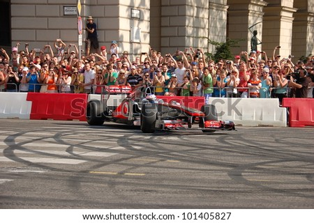 BUDAPEST, HUNGARY-  MAY 1: F1 driver Jenson Button does some burnouts for his fans on May 1, 2012 on streets in Budapest. - stock photo