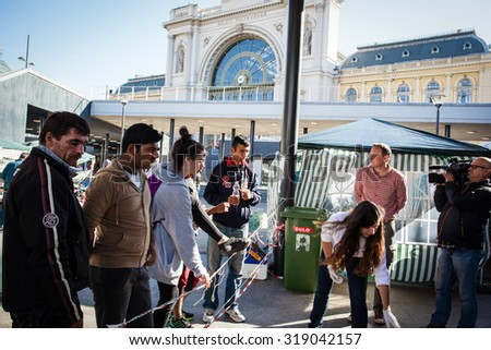 BUDAPEST - SEPTEMBER 7: war refugees reading go Wien text at Keleti Railway Station on 7 September 2015 in Budapest, Hungary. Refugees are arriving constantly to Hungary on the way to Germany. - stock photo