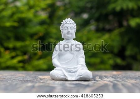 Buddha - ceramic statuette budha on green background. Buddhism, meditation and yoga concept - stock photo