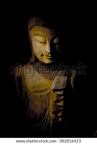 Buddha face in Light, wood carving of a sculpture of Buddha with focus on the downcast eye, very shallow depth of field. - stock photo