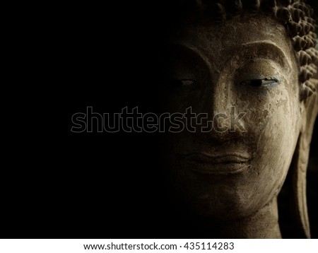 Buddha face with light and shadow on black background. - stock photo