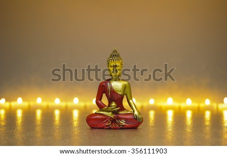 Buddha figure sitting in front of burning candle lights - stock photo