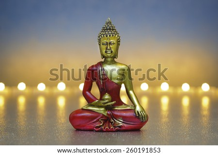 Buddha figure with candle lights in row - stock photo