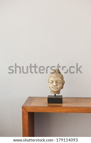 Buddha head on side board in front of a grey wall  - stock photo